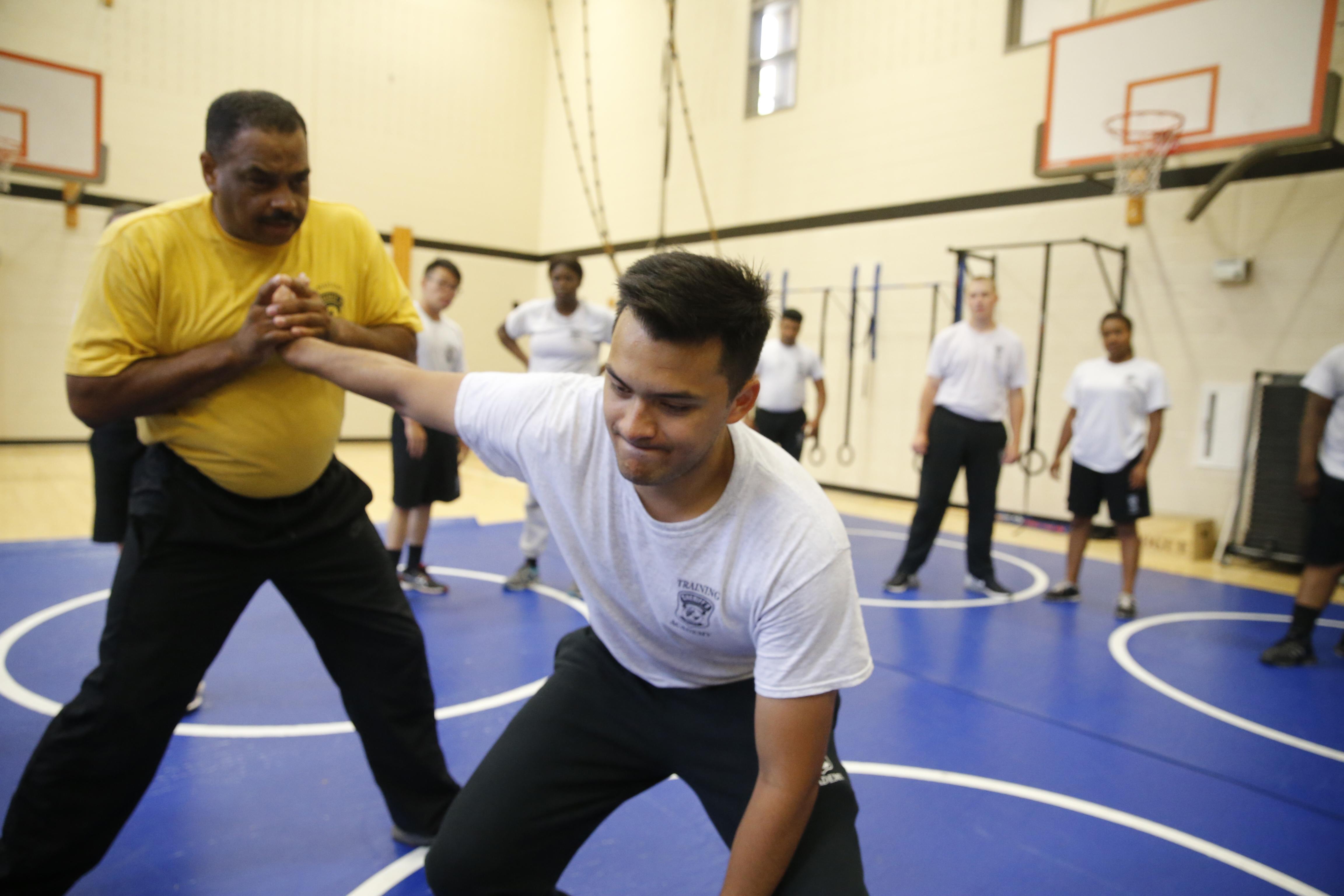 Academy recruit, Agustin Hussain, right, is subdued by Sergeant David Turner, left, during a course on the the finer points of hand-to-hand defensive techniques on July 13.